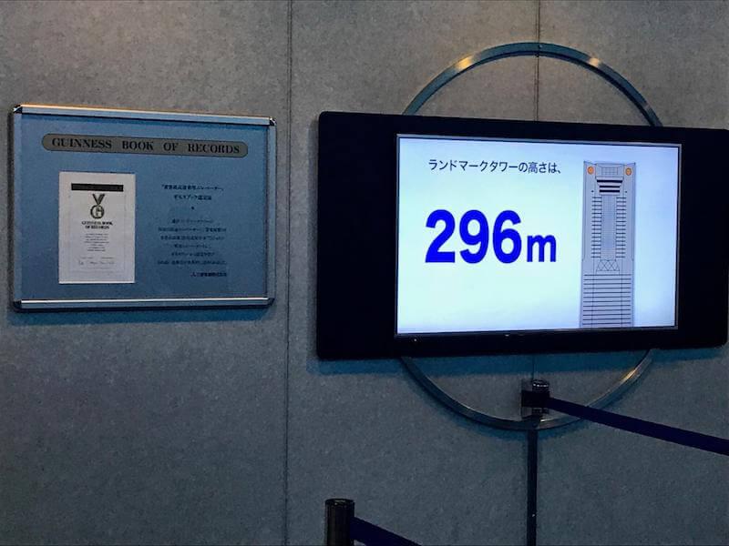 ランドマークタワーの高さは296mと示すTVモニター